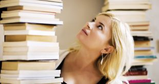 Woman looking at the pile of books.